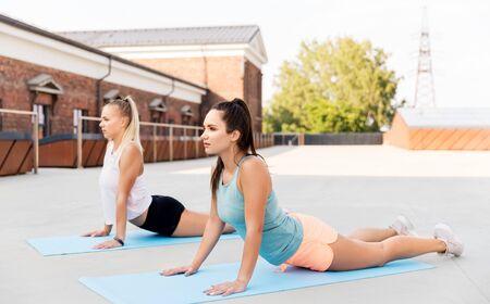 Photo pour women doing sports on exercise mats outdoors - image libre de droit
