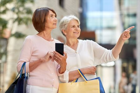 Photo pour old women with shopping bags and cellphone in city - image libre de droit