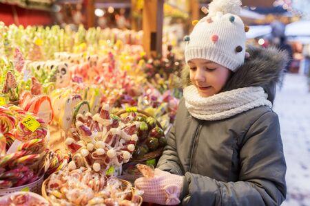 Photo pour Happy little girl with lollipop at christmas market candy shop in evening - image libre de droit