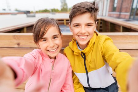 Photo for children sitting on street bench and taking selfie - Royalty Free Image