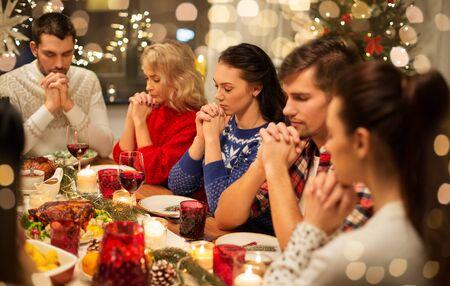 Photo pour friends having home christmas dinner and praying - image libre de droit