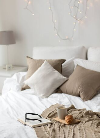 Photo pour comfort, hygge and interior concept - coffee, croissant, blanket and book on bed at cozy home - image libre de droit