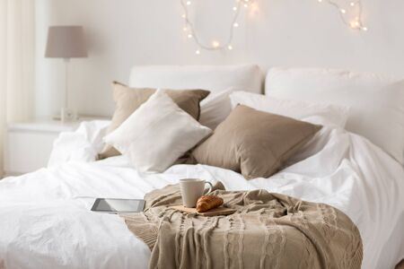 Photo pour comfort, hygge and interior concept - tablet computer, cup of coffee and croissant on bed at cozy home - image libre de droit