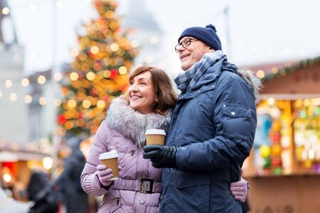 Foto de love, winter holidays and people concept - happy senior couple with takeaway coffee at christmas market on town hall square in tallinn, estonia - Imagen libre de derechos
