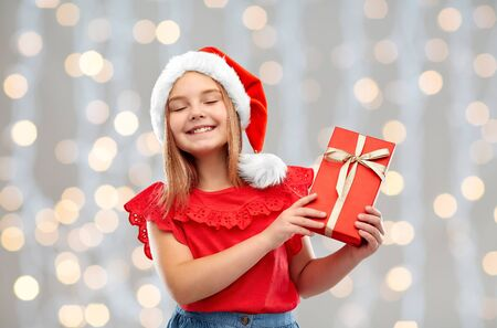 Photo for christmas, childhood and holidays concept - smiling pleased girl posing in santa helper hat with gift box over festive lights background - Royalty Free Image