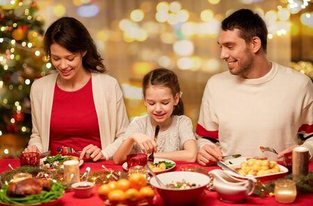 Foto de happy family having christmas dinner at home - Imagen libre de derechos