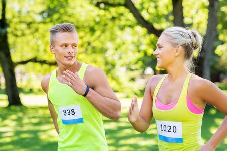 Foto de happy couple of sportsmen racing wit badge numbers - Imagen libre de derechos