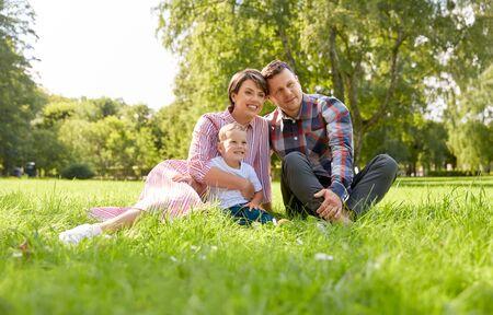 Photo pour happy family at summer park sitting on grass - image libre de droit