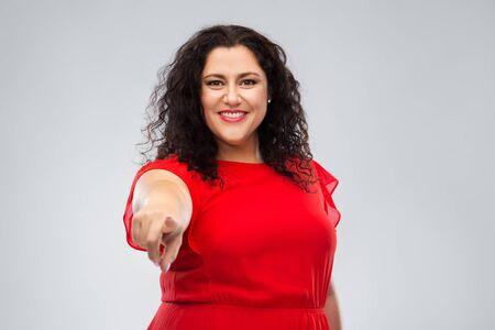 Foto de happy woman in red dress pointing finger to you - Imagen libre de derechos
