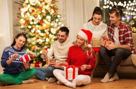 Photo pour friends celebrating christmas and opening presents - image libre de droit
