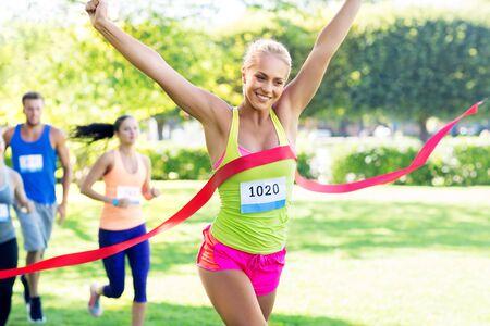 Photo pour happy young female runner on finish winning race - image libre de droit