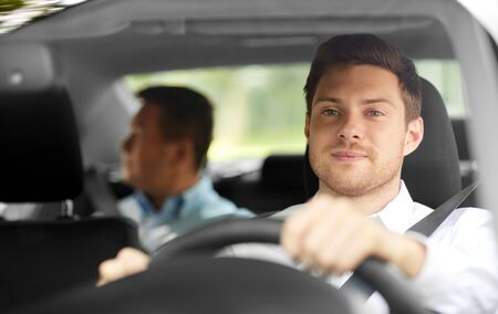 Foto de male taxi driver driving car with passenger - Imagen libre de derechos