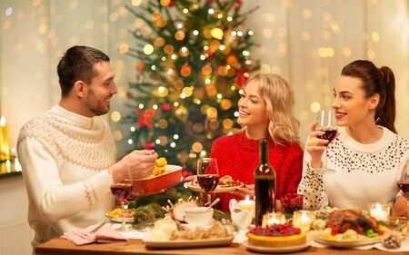 Photo pour holidays and celebration concept - happy friends having christmas dinner at home, eating and drinking - image libre de droit