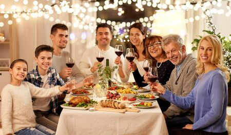 Photo pour celebration, holidays and people concept - happy family having dinner party, drinking red wine and toasting at home - image libre de droit