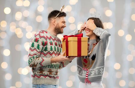 Photo for happy couple in ugly sweaters with christmas gift - Royalty Free Image