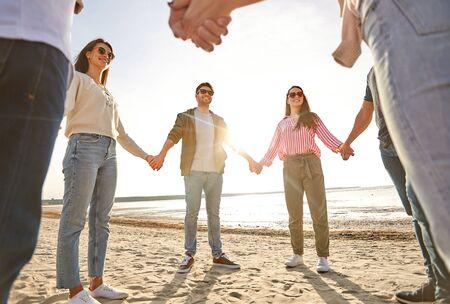 Photo pour happy friends holding hands on summer beach - image libre de droit