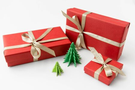 Foto für winter holidays, new year and celebration concept - red gift boxes and origami christmas trees on white background - Lizenzfreies Bild