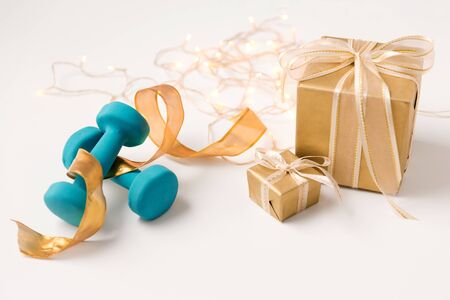Photo for winter holidays, new year and christmas concept - gift boxes wrapped into golden paper and blue dumbbells on white background - Royalty Free Image