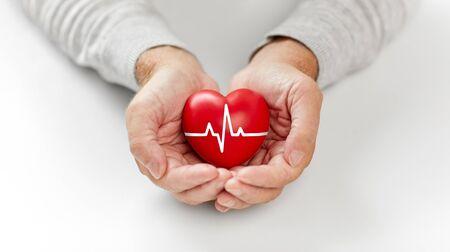 Photo pour senior man holding red heart with ecg line - image libre de droit