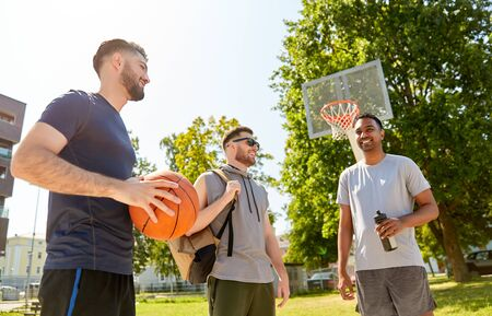 Photo pour sport, leisure games and male friendship concept - group of men or friends going to play basketball outdoors - image libre de droit