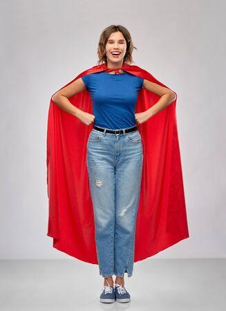 Foto de women's power and people concept - happy woman in red superhero cape over grey background - Imagen libre de derechos
