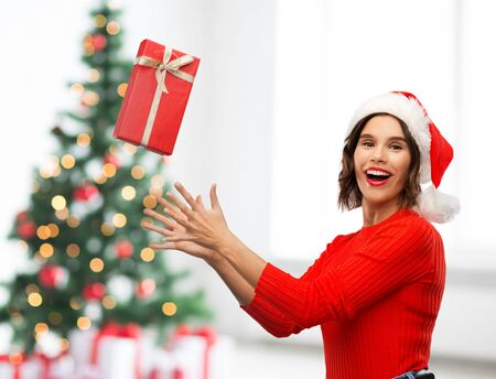 Photo for greetings and winter holidays concept - happy smiling young woman in santa helper hat catching red gift box over christmas tree lights background - Royalty Free Image