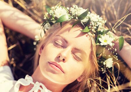 Photo for nature, summer holidays, vacation and people concept - happy smiling woman in wreath of flowers lying on straw - Royalty Free Image