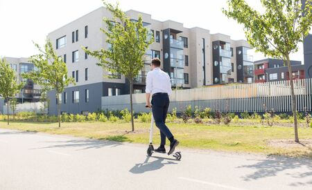 Photo pour business and people and concept - young businessman riding electric scooter outdoors - image libre de droit
