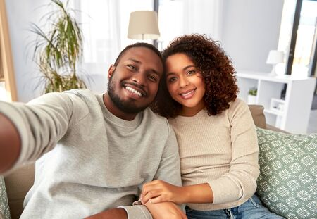 Photo for family, technology and people concept - happy african american couple taking selfie at home - Royalty Free Image
