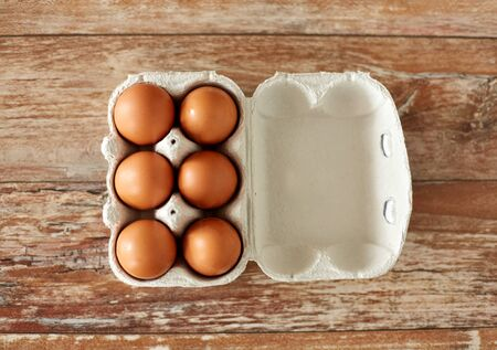 Photo for close up of eggs in cardboard box on wooden table - Royalty Free Image