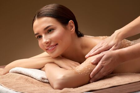 Photo pour wellness, beauty and relaxation concept - happy young woman having exfoliating salt massage at spa - image libre de droit