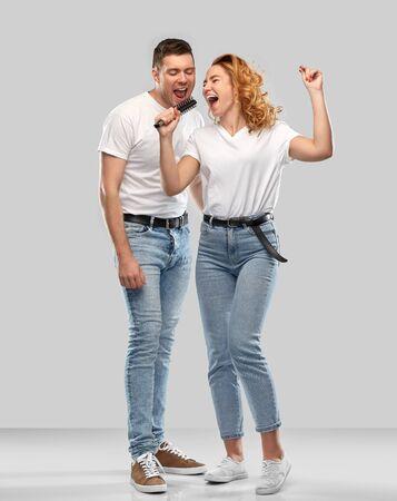 Photo pour happy couple singing to hairbrush - image libre de droit