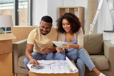 Photo pour couple with blueprint counting money at home - image libre de droit