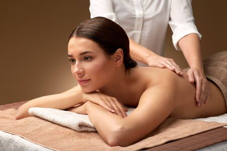 Foto de wellness, beauty and relaxation concept - beautiful young woman lying and having back massage at spa - Imagen libre de derechos