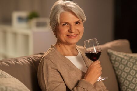 Foto per people, alcohol and drinks concept - happy smiling senior woman drinking red wine from glass at home in evening - Immagine Royalty Free