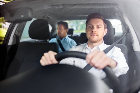 male driver with wireless earphones driving car