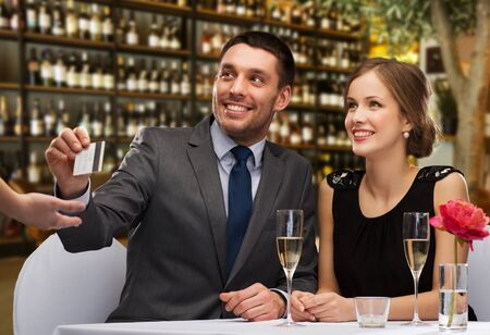 Photo pour Happy couple paying with credit card at restaurant - image libre de droit