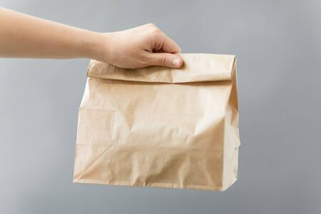 Photo for recycling and ecology concept - hand holding disposable brown takeaway food in paper bag with lunch on table - Royalty Free Image