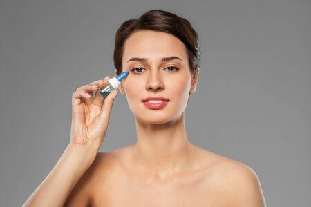 Photo pour beautiful young woman with eye drops - image libre de droit