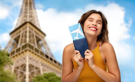 Photo pour travel, tourism and vacation concept - happy smiling young woman in yellow top with air ticket and passport over eiffel tower in paris, france background - image libre de droit