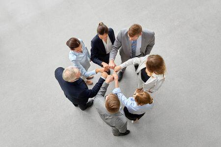 Photo pour corporate, people and teamwork concept - happy business team making fist bump - image libre de droit