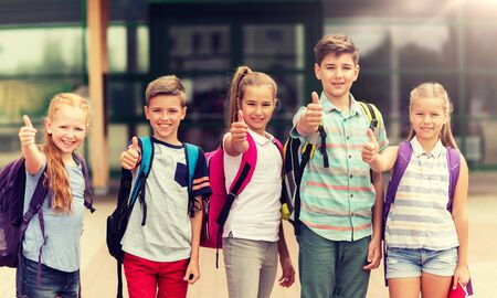 Photo pour primary education, friendship, childhood, gesture and people concept - group of happy elementary school students with backpacks showing thumbs up outdoors - image libre de droit