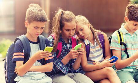 Photo pour elementary school students with smartphones - image libre de droit