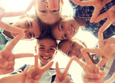 Photo pour group of happy children showing v sign in circle - image libre de droit