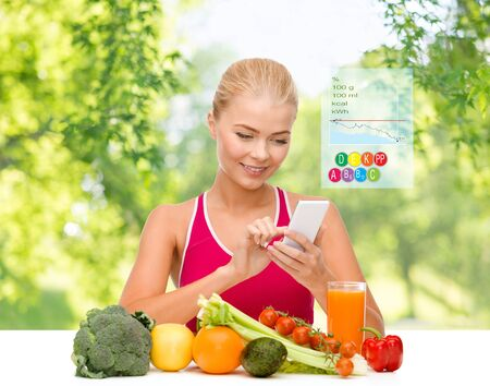 Photo for woman with vegetables pointing at smartphone - Royalty Free Image