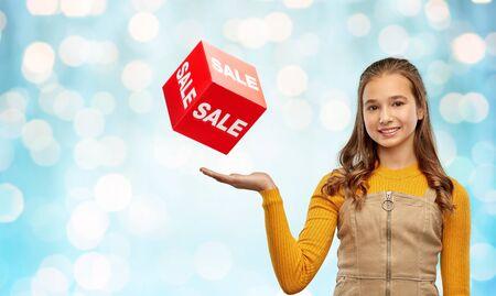Photo pour happy teenage girl showing sale sign - image libre de droit