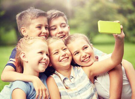 Photo pour happy kids or friends taking selfie in summer park - image libre de droit