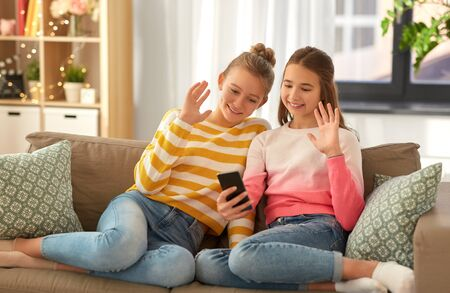 Photo pour girls having video call on smartphone at home - image libre de droit