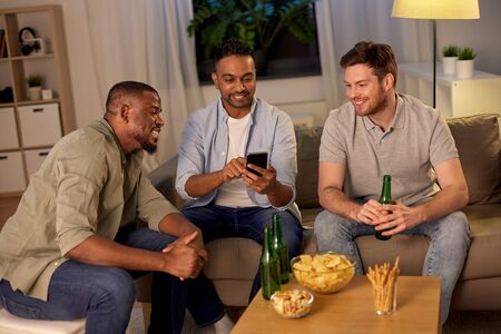 Photo for male friends with smartphone drinking beer at home - Royalty Free Image