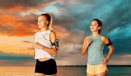 Photo pour young women with earphones and smartphones running - image libre de droit